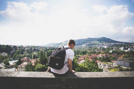 man met rugzak op de achtergrond van de stad